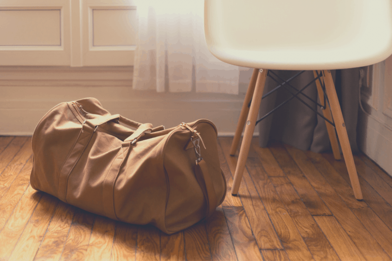brown duffel bag on wood floor by a draped window and a white chair